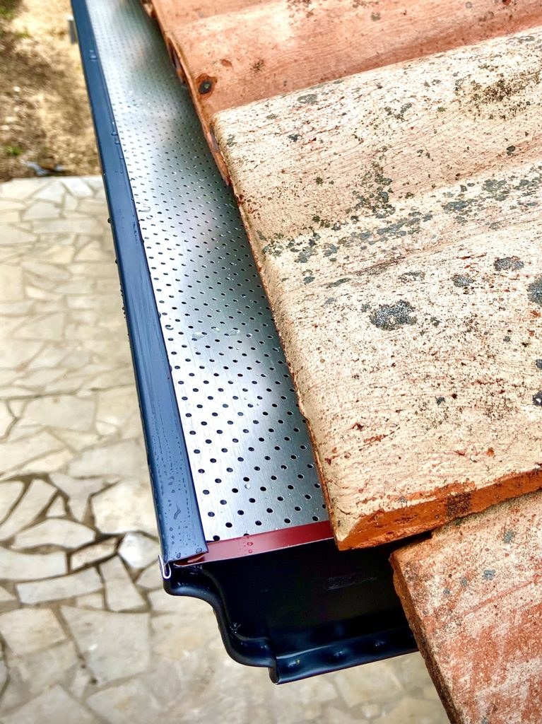 Pose de grilles pares feuilles sur une gouttière corniche de couleur bleu ardoise.